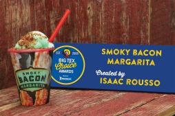 An unconventional pairing of flavors adds a subtle smoky taste to a traditionally tangy drink. The Smoky Bacon Margarita takes the smokiness of freshly-cooked bacon and infuses it into a frozen lime margarita. With just a hint of smoke, this drink still captures the zesty citrus flavor of a traditional margarita. Finished off with a pinch of bacon crumbles on top, this thirst-quenching drink is served in a collectible souvenir cup for an added funky flair. Sip on this refreshing beverage and cool off from the Texas heat! Contains alcohol – must be 21 years of age.