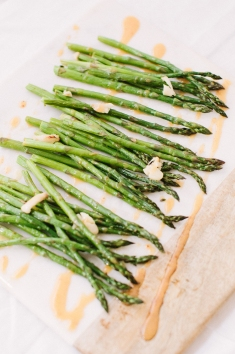 Lemon Garlic Asparagus - This tender asparagus side is marinated in a lemon vinaigrette and roasted with plenty of smashed garlic.