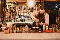 Master behind the bar, Mike Sturdivant strains the Green Eggs and Hami cocktail.