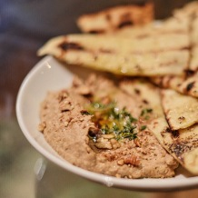 Black Garlic Hummus with candied pecans, EVOO, and grilled house flatbread. Perfectly creamy and garlic-y. Perfect for any garlic lover.